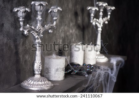 Tarantula Spider on Eerie Cobweb Covered Mantle with Candles and Candelabras in Haunted House Setting - stock photo