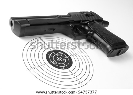 Target with holes and gun - stock photo