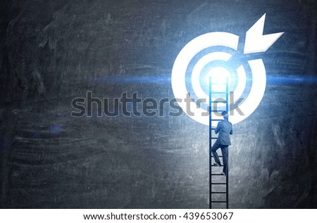 Targeting concept with businessman climbing ladder to abstract illuminated dartboard sketch on chalkboard - stock photo