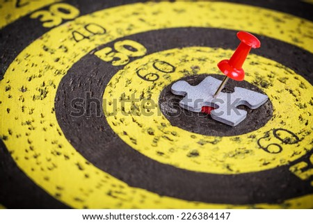 Targeting customers concept: red pin stuck to a man shape jigsaw puzzle piece on old target board - stock photo