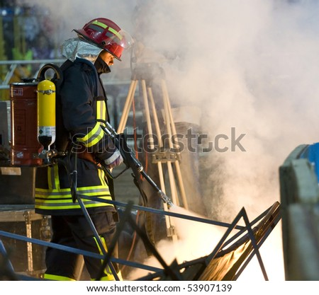 TARGU-JIU, ROMANIA - JUNE 13: Fireman with extinguisher fighting a fire during the Romanian Cup Final soccer game, June 13, 2009 in Targu-Jiu, Romania - stock photo
