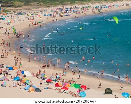 Tarifa, SPAIN -JULY 25, 2014: Beach Punta Paloma of Tarifa crowded with people sunbathing and doing wind and kite surf - stock photo