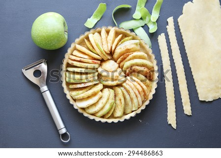 Tart dish with pastry base and apple filling before baking.Top view - stock photo