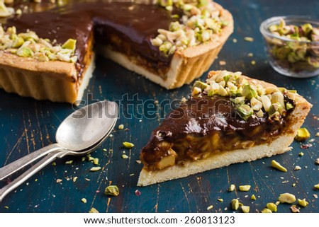 Tart with caramel, chocolate and nuts - stock photo