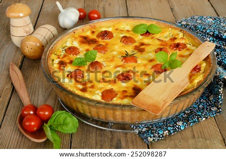 Tart with cheese and cherry tomatoes. Pie with cottage cheese and tomato on wooden table - stock photo