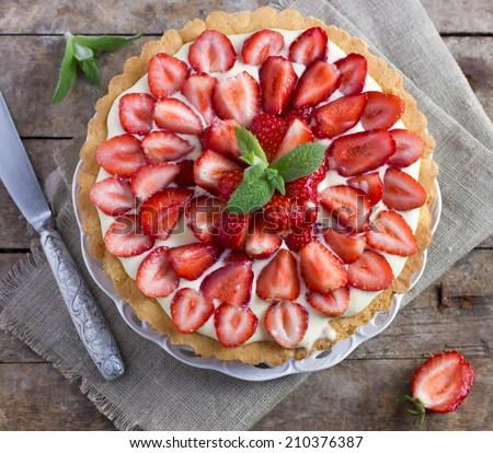 tart with cream and fresh strawberries on the  old wooden background, top view square image - stock photo