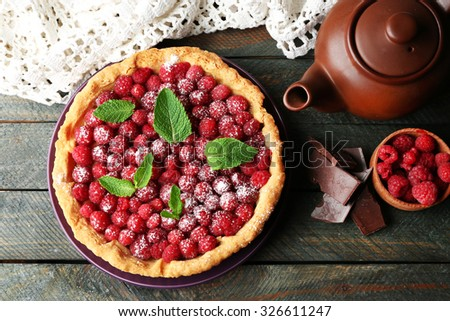 Tart with fresh raspberries and teapot, on wooden background - stock photo