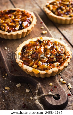 Tart with nuts and caramel on a rustic  background - stock photo