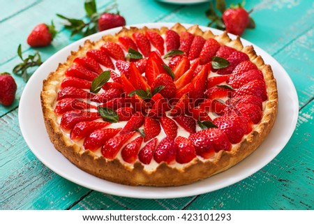 Tart with strawberries and whipped cream decorated with mint leaves.  - stock photo