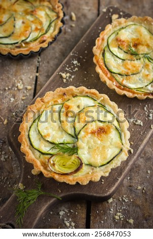 tart with zucchini, leek and cheese on rustic background, top view - stock photo