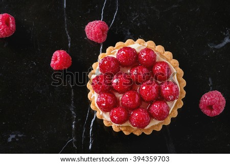 Tartlet with custard and fresh glazed raspberries, served on black marble surface. Top view - stock photo