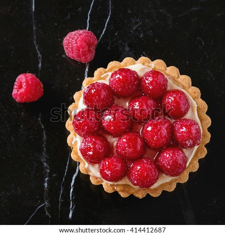 Tartlet with custard and fresh glazed raspberries, served on black marble surface. Top view. Square image - stock photo