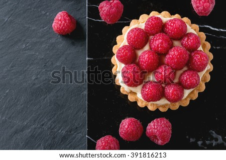 Tartlet with custard and fresh ripe raspberries, served on black marble board over stone slate surface. With copy space at left.Top view - stock photo