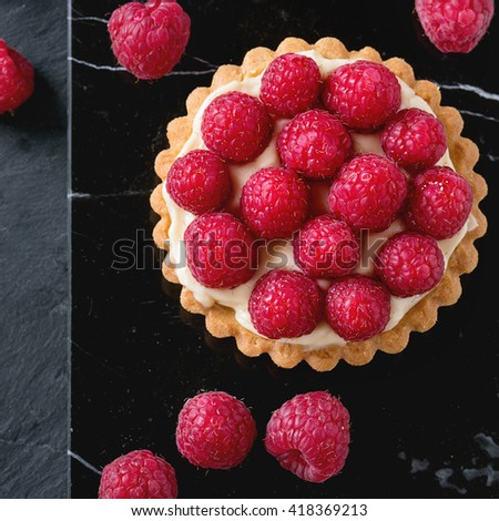Tartlet with custard and fresh ripe raspberries, served on black marble board over stone slate surface. With copy space at left.Top view. Square image - stock photo