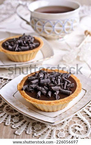 Tartlet with dark chocolate on a white saucer - stock photo