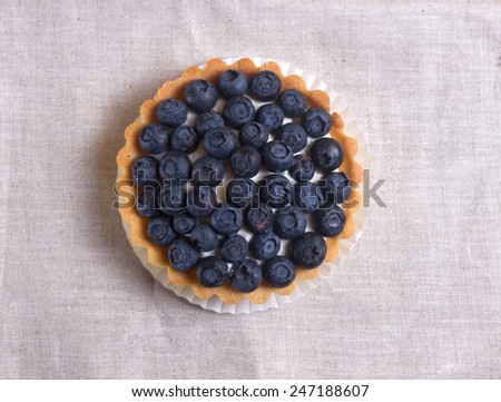 Tartlet with fresh blueberries on a wooden background  - stock photo