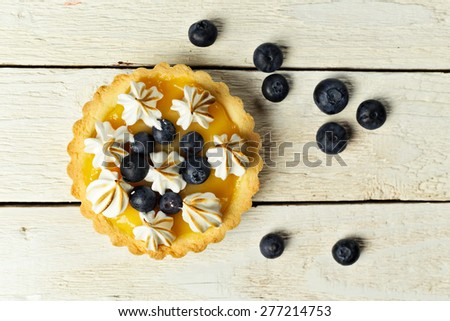 Tartlet with lemon curd, blueberries and meringue top view - stock photo