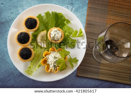 Tartlets filled with black caviar and cheese and dill salad on white plate and leaf against blue rustic wooden background with a wine glass on bamboo placemat, horizontal top view - stock photo