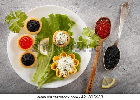 Tartlets filled with black caviar and cheese and dill salad on white plate and leaf against silver rustic wooden background with  silver and wooden spoons full of caviar, horizontal top view - stock photo