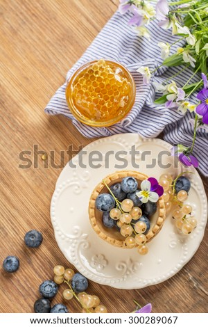 Tartlets of pastry with blueberries and currants with fresh honey honeycombs on a wooden background. selective Focus - stock photo