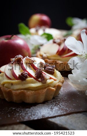 Tartlets with apple slices, cream and pecan filling - stock photo