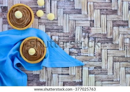 Tartlets with chocolate cream and macadamia nuts. Top view - stock photo