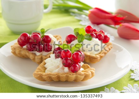 Tartlets with cream and currants. - stock photo