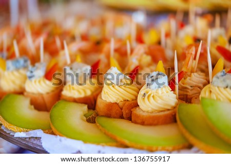 Tartlets with cream, cheese and melons on festive table for Christmas. - stock photo