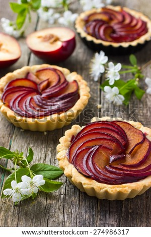 Tartlets with plum on old wooden background - stock photo
