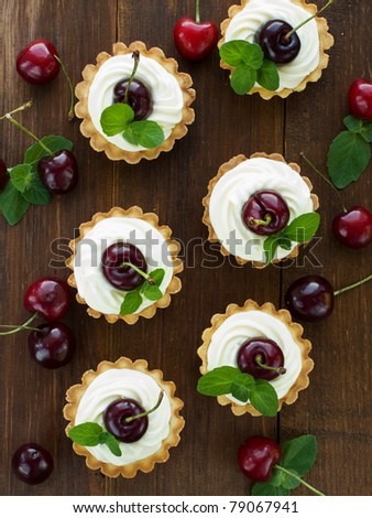 Tartlets with sweet cherries, whipped sour cream and mint. Viewed from above. - stock photo