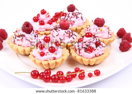 Tartlets with whipped cream, fruits and sprinkles - raspberries and redcurrants - stock photo