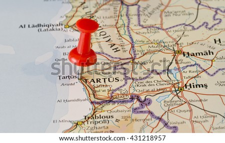 Tartus marked on map with red pushpin. Selective focus on the word Tartus and the pushpin. Pin is in an angle. Midground is sharp while foreground and background is blurry. - stock photo