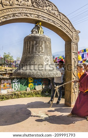 TASHIDING, INDIA - MARCH 16, 2014: A monch at bumchu festival, Tashiding, Sikkim, is ringing the big prayer bell. In the background are prayer flags and mani stones. - stock photo