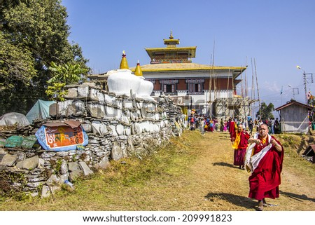 TASHIDING, INDIA - MARCH 16, 2014: monchs are coming out of the temple along a mani wall. A wall, engraved with buddhist prayers. - stock photo
