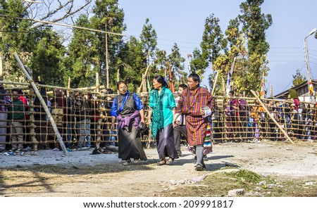 TASHIDING, INDIA - MARCH 16, 2014: Tibetan pilgrims at the bumchu festival, Tashiding, Sikkim. In the background buddhist believers are queuing in two lines to get into the temple. - stock photo