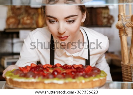 Taste of France. Closeup selective focus shot of a baker holding a box of colorful macaroons  - stock photo