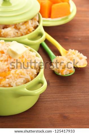 Taste rice porridge with pumpkin in saucepans on wooden background - stock photo
