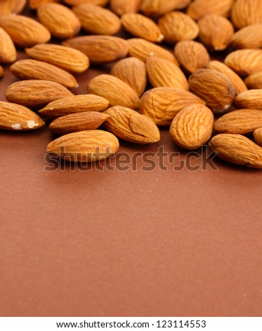 tasty almond nuts, on brown background - stock photo