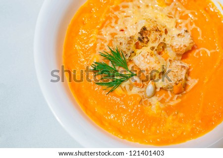 Tasty and delicious squash pumpkin soup with toasts, melted cheese, decorated with dill and pumpkin seeds in white plate against white tablecloth background. Focus on toast. Copy space - stock photo