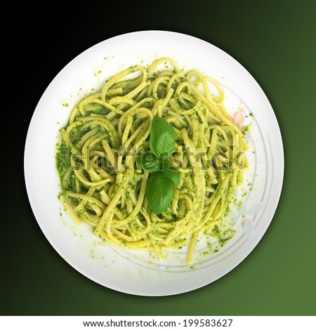 Tasty and ever delicious  Italian recipe: linguine with pesto sauce, condiment prepared on the spot (using mortar and pestle) with fresh basil, olive oil, garlic, pine nuts and parmesan cheese - stock photo