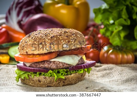 Tasty and fragrant hamburger meat in a healthy integral bread. With the fresh tomatoes, onion and lettuce with the addition of fried chips. - stock photo