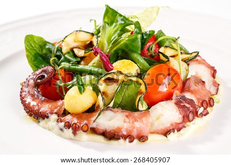 Tasty and fresh. Close-up of octopus salad with lettuce, zucchini, asparagus, mash-salad and tomatoes cherry - stock photo