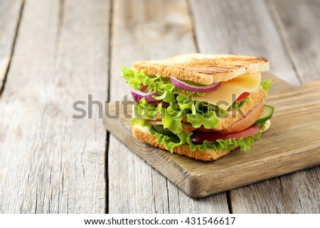 Tasty and fresh sandwiches on a grey wooden table - stock photo