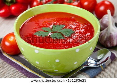 Tasty and healthy tomato soup and vegetables on the table - stock photo