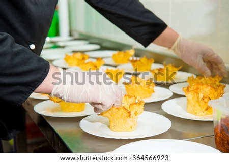 tasty appetizer. The process of filling tartlets stuffed chef restaurant. hands fill and decorate the dish. in  restaurant kitchen. Holiday Appetizers with ham, pepper, olive, crab, octopus, greenery - stock photo