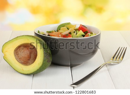 Tasty avocado salad in bowl  on wooden table on natural background - stock photo