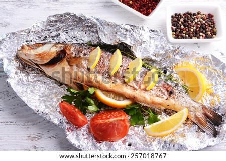 Tasty baked fish in foil on table close-up - stock photo