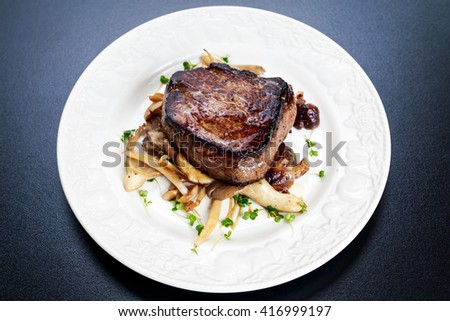 Tasty Beef Mignon steak with mushrooms and herbs on plate - stock photo