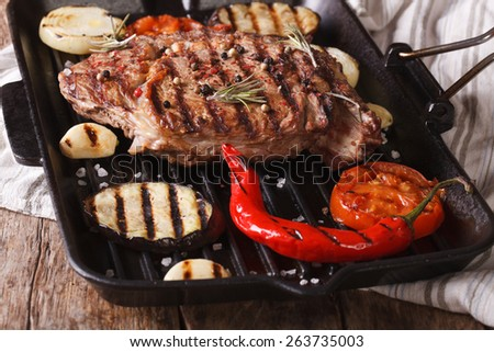 Tasty beef steak with vegetables on a grill pan closeup. horizontal.  - stock photo