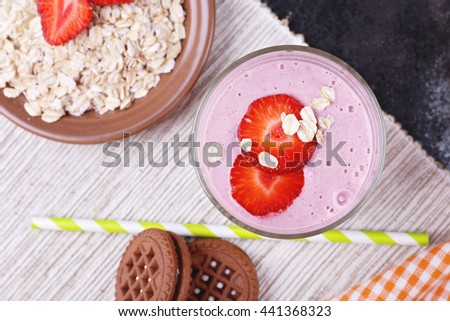 Tasty berry smoothie yogurt with oat flakes for breakfast. Jar with milkshake with strawberries slices. Delicious and healthy breakfast on the table on the napkin. - stock photo